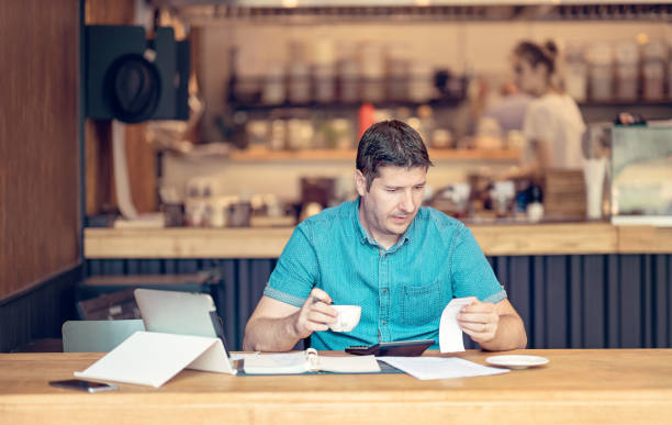 Accountant looking worried over the profit and loss accountancy papers stock photo