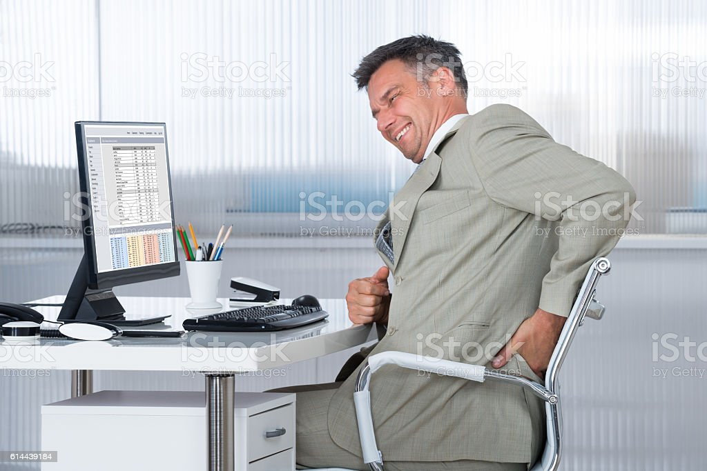 Accountant Suffering From Back Pain At Desk stock photo