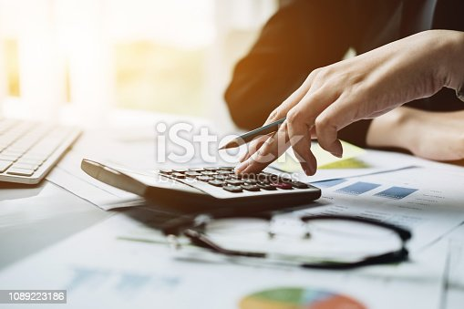 istock Accountant with calculator counting making notes at office hand is writes in a postit sticky 1089223186