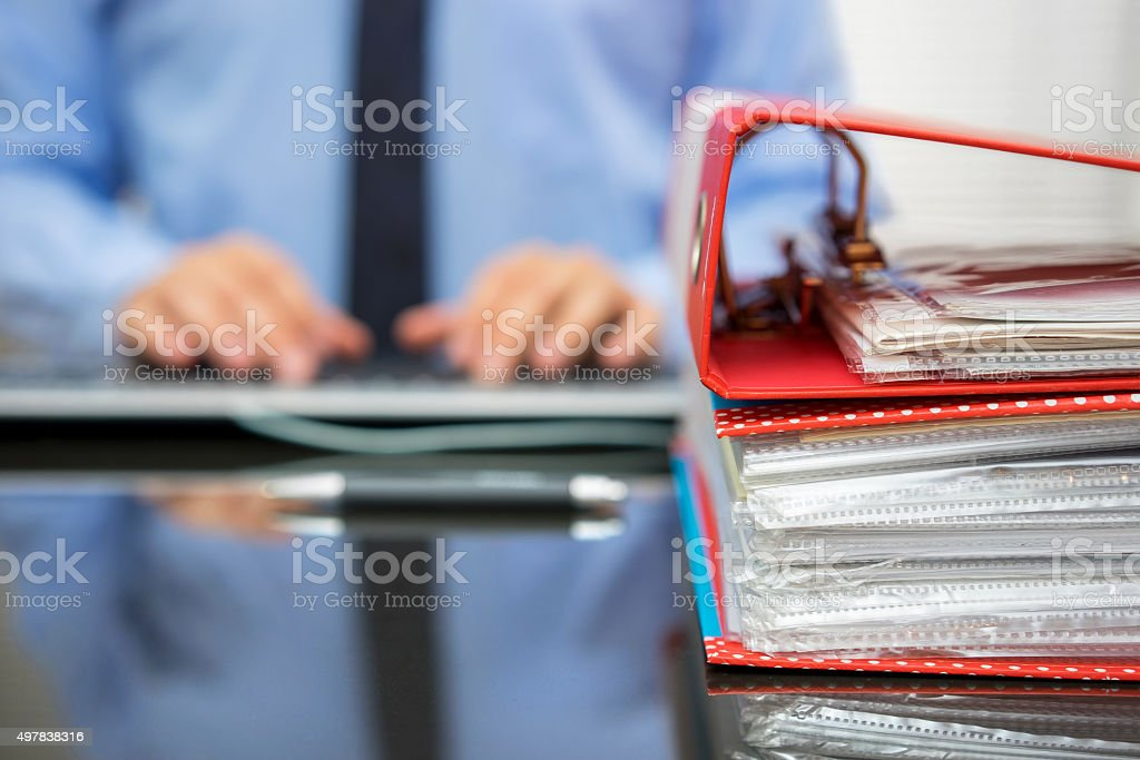 accountant with stack of invoices is inserting data into computer stock photo