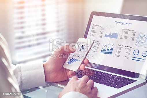 istock Accountant working on consolidated financial report of corporate operations, consultant auditing finance data (balance sheet, income statement) on screen with business charts, fintech, manager 1144567782
