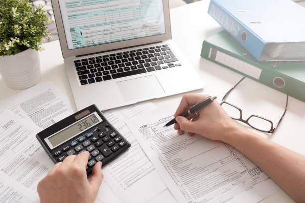 akuntan yang bekerja dengan formulir pajak as - cpa vs tax advisor potret stok, foto, & gambar bebas royalti