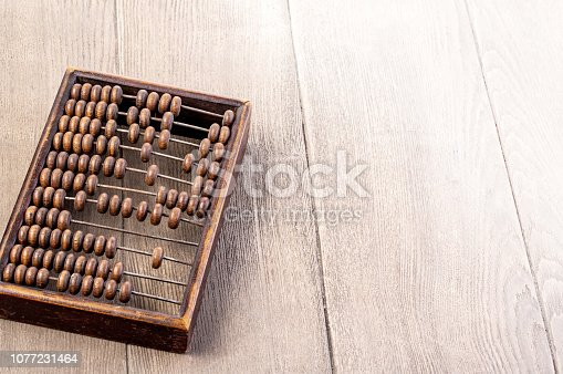 istock Accounting abacus on wooden textured background 1077231464