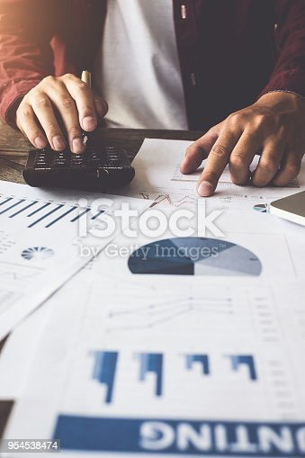 istock Accounting concept. Close up Businessman using pen and calculator for do math finance on wooden desk. 954538474