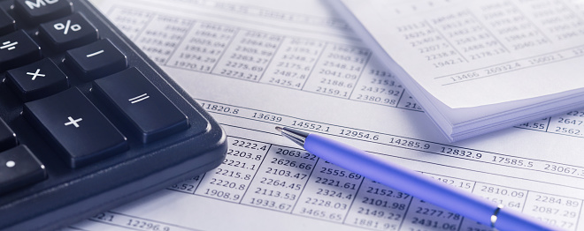 accounting document with pen and calculator. Concept of banking, financial report and financial audit.