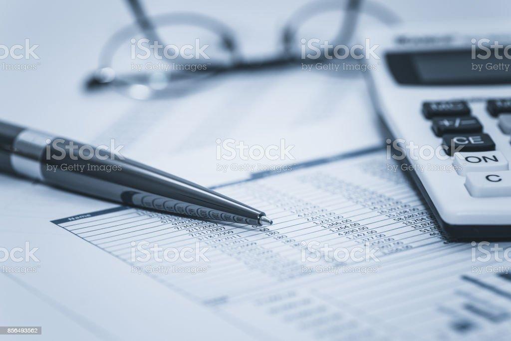 Buchhaltung Finanzprüfung Bank banking Konto Lager Tabellendaten mit Brille Stift und Taschenrechner in gewaschenen blauen monochrome Finanzkonzept für Analyse, Prüfung finanzieren Forensik - Lizenzfrei Analysieren Stock-Foto