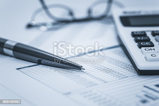 istock Accounting financial audit bank banking account stock spreadsheet data with glasses pen and calculator in washed blue monochrome financial concept for analysis, audit finance forensics 856493562