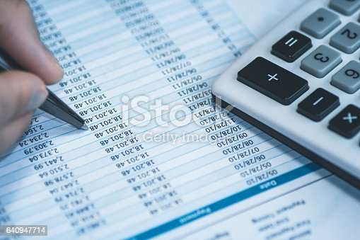 istock Accounting financial banking stock spreadsheet data with human hand holding pen and calculator in blue. 640947714