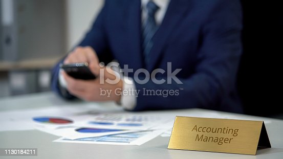 1130184417 istock photo Accounting manager using smartphone, checking data for report, papers on table 1130184211