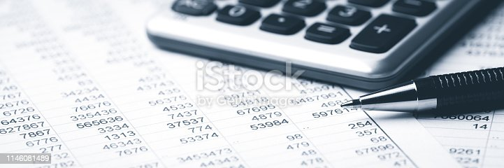 Pen and calculator lying on a business paper with numbers. Tax document.