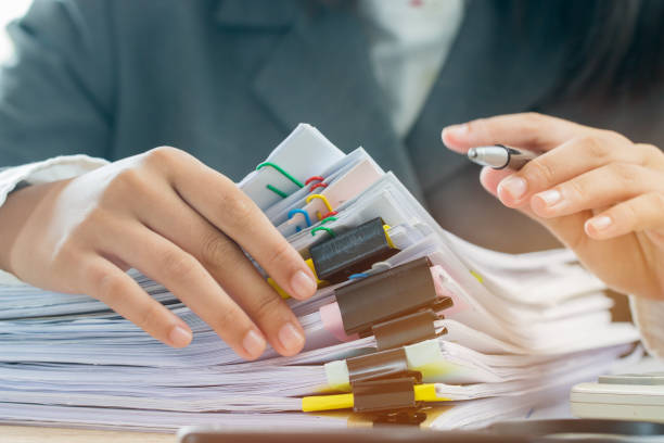 Accounting planning budget concept : Business woman offices working for arranging documents unfinished stack of document papers with pen, calculator, clip papers on busy office desk stock photo