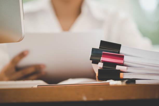 buchhaltung planung budget-berichts-konzept: business frauen büros prüfen die arbeit für die anordnung von dokumenten unfertigen stapel von dokumentenpapieren mit stift auf belebten büro mit pc-computer. - publikation stock-fotos und bilder