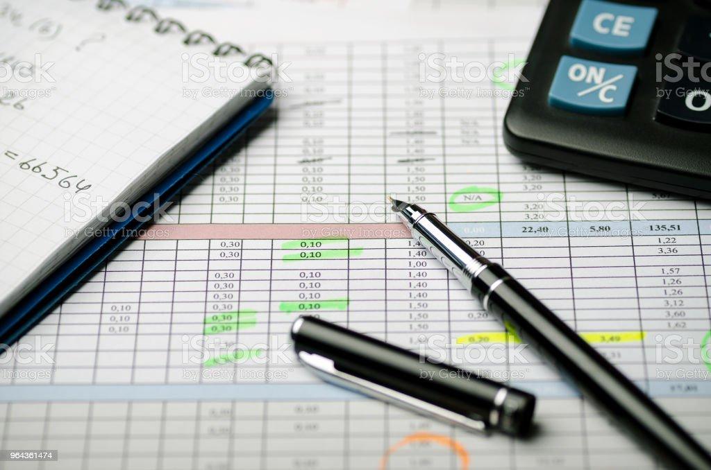 Registos contabilísticos em tabelas, um caderno de papel com cálculos e uma caneta preta - Foto de stock de Ajustando royalty-free