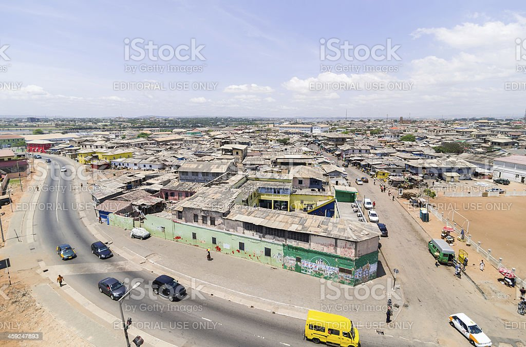 """Accra from Above """"Accra, Ghana - October 17, 2012: Accra from Above. Skyline of Jamestown a part Accra in Ghana, as seen from the old lighthouse. A curved road, traffic, streetlife and the old Sea View Hotel can be seen. People on the sidewalk busy with their daily activities."""" Accra Stock Photo"""