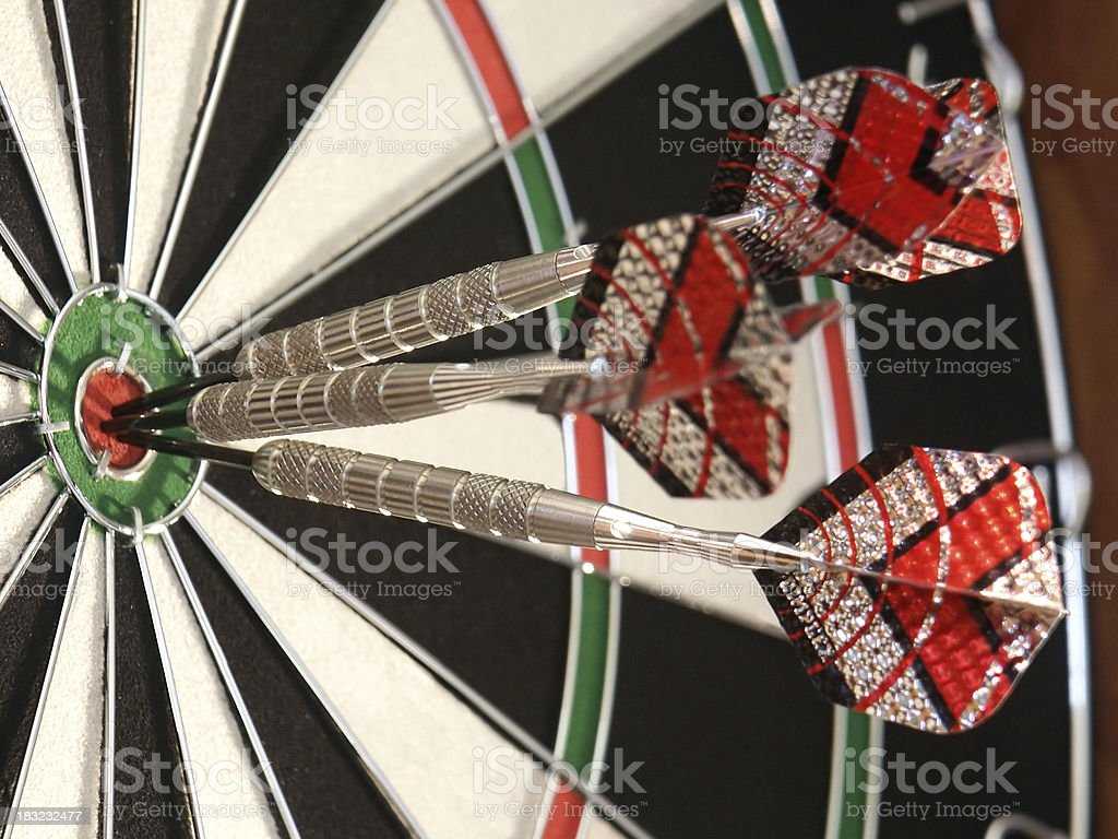 Three darts hitting the bullseye on a dartboard.