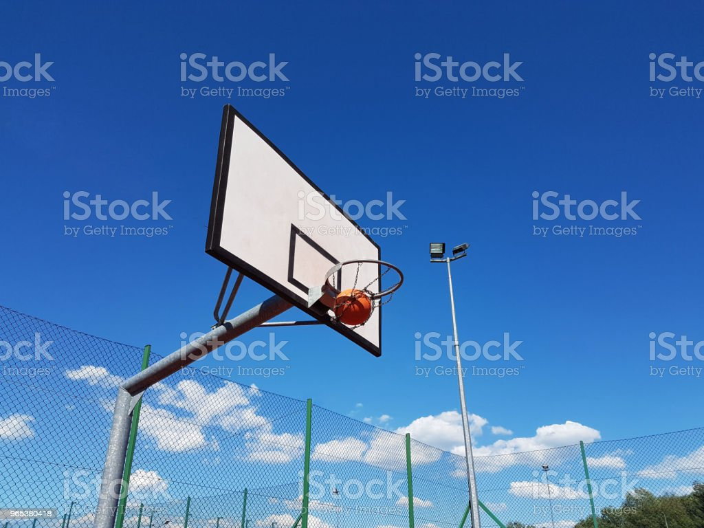 Accurate throw the ball into the basketball ring at the stadium in the open air on a sunny clear day. royalty-free stock photo