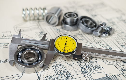 Analog metallic measuring instrument with yellow round dial. Group of steel components on document. Precise calliper. Selective focus