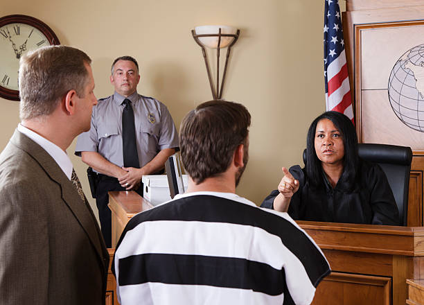 accused criminal and lawyer in a courtroom - four lawyers stockfoto's en -beelden