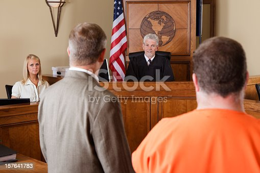 A lawyer standing with his client before the judge in a criminal trial.