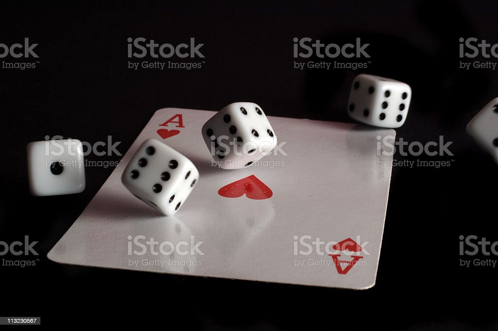 ace of hearts and spinning dice against black stock photo
