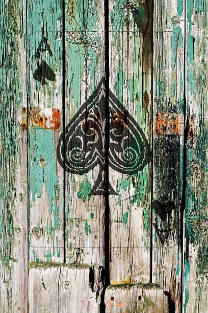 Un as de pique dans la vieille porte en bois - Photo