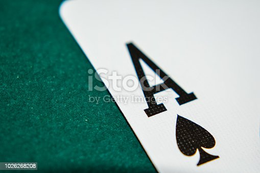 The Ace of spades on a green poker table up close.
