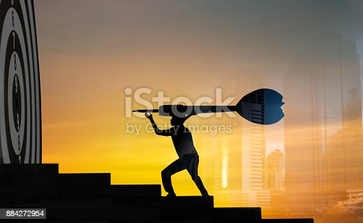 istock Achievement and goal concept, silhouette of businessman holding dart to  goal board 884272954