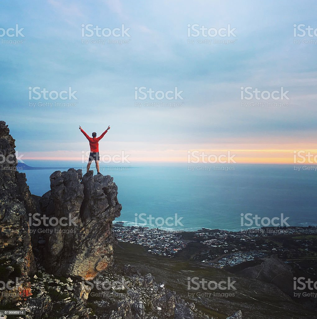 Achievement - male standing on a mountain top stock photo