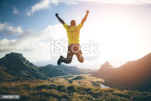 Success, achievement concept. Man jumping in the air on top of the mountain, hands raised up, mountain landscape on background.