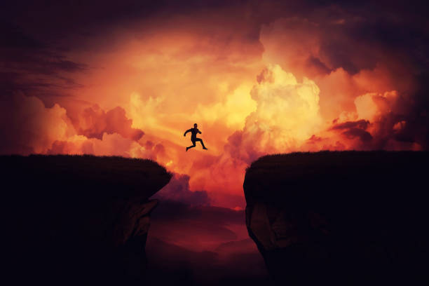 Achieving goals Fantasy self overcome concept as a businessman jump over a chasm obstacle above the clouds. Way to win and succes over sunset background. Achieving goals symbol. ravine stock pictures, royalty-free photos & images