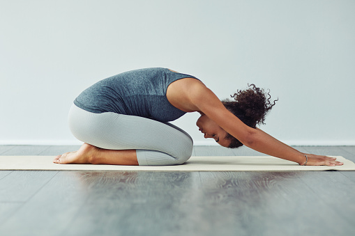 Studio shot of an attractive young woman practicing yoga against a grey background