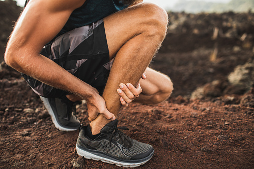 istock Achilles injury on running outdoors. Man holding Achilles tendon by hands close-up and suffering with pain. Sprain ligament or Achilles tendonitis. 1158317155