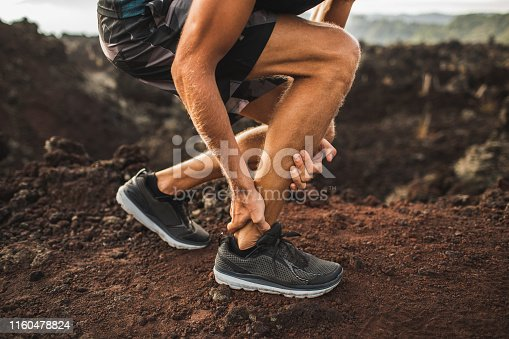 istock Achilles injury on running outdoors. Man holding Achilles tendon by hands close-up and suffering with pain. Sprain ligament or Achilles tendonitis. 1160478824
