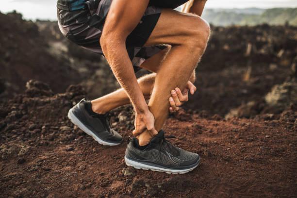 屋外走行中のアキレスけが。手をクローズアップし、痛みに苦しむアキレス腱を保持している男。捻挫靭帯またはアキレス腱炎。 - 脛 ストックフォトと画像