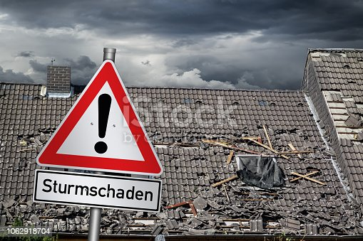 istock Achtung Sturmschaden german red warning sign in front of  storm damaged roof  ( english translation: attention storm damage ) 1062918704