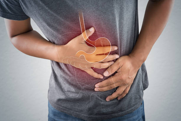 acid reflux or heartburn, the photo of stomach is on the men's body against gray background, bad health, male anatomy concept - acid stock pictures, royalty-free photos & images