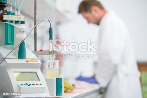 Researcher Using Acidity Measuring Machine for Grape Research.