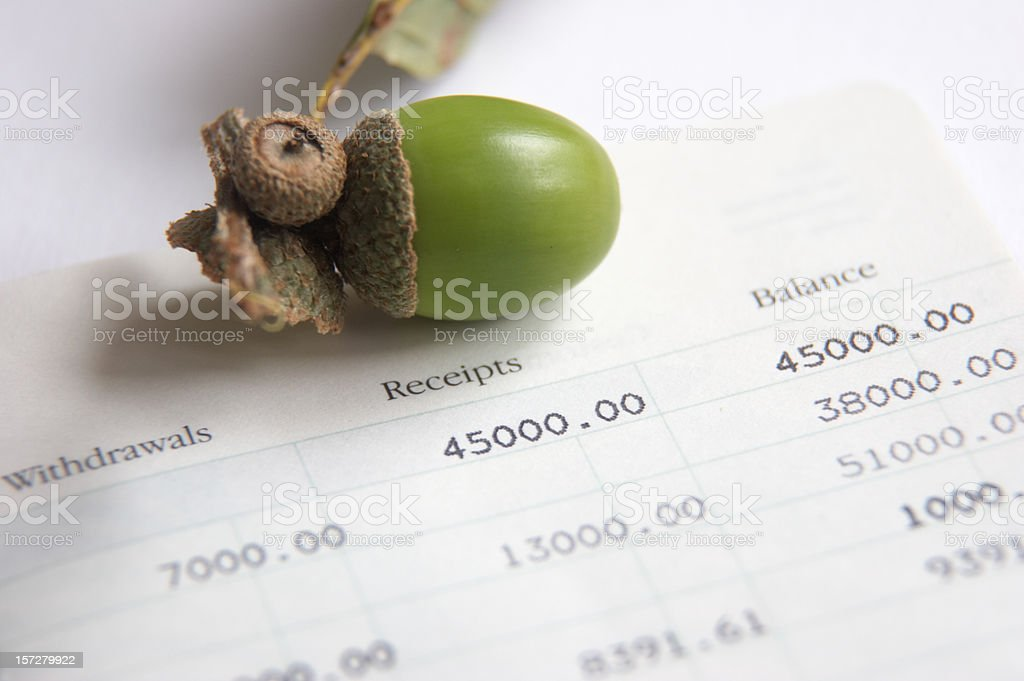 Acorn (on top) and savings growth concept stock photo