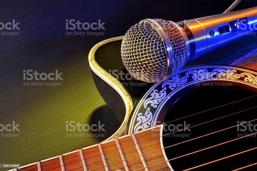 Acoustic guitar and microphone isolated with yellow and blue lig - foto de stock