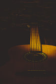 Acoustic guitar close-up in the dark, illuminated by a beam of light.