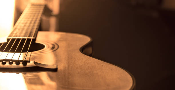 acoustic guitar close-up on a beautiful colored background acoustic guitar close-up on a beautiful colored background, the concept of stringed instruments country and western music stock pictures, royalty-free photos & images
