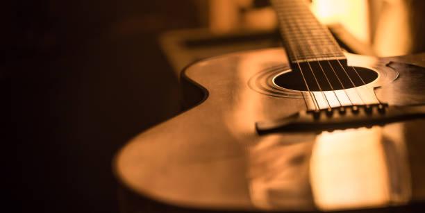 美しい色の背景にアコースティックギタークローズアップ - ギター ストックフォトと画像