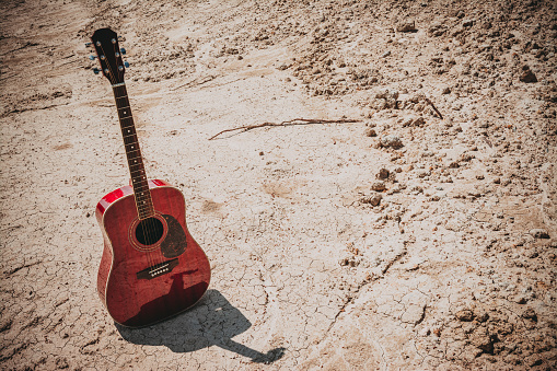 istock acoustic guitar lying on a desert land, vintage style with copy space 968906102