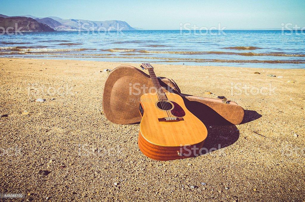 Acoustic guitar on a beach stock photo