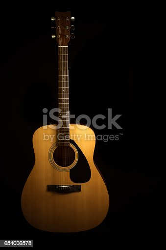 istock Acoustic guitar on a black background with copy space 654006578