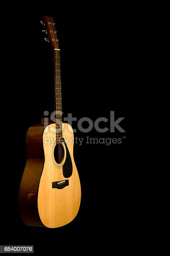 istock Acoustic guitar on a black background with copy space 654007076