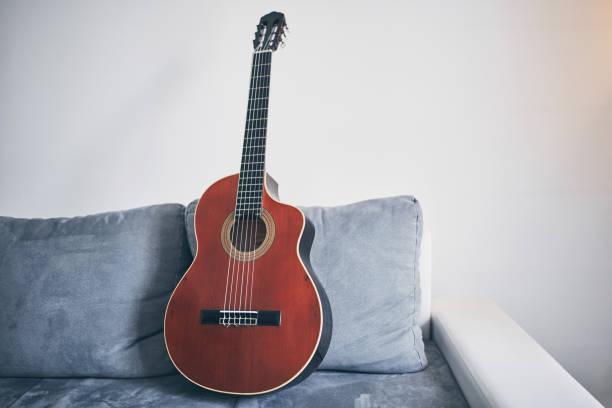 Akustische Gitarre auf einer Wohnzimmercouch / Sofa. – Foto