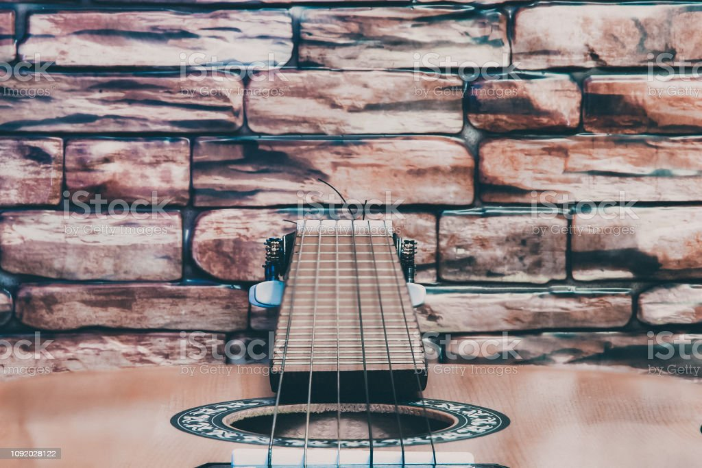 Acoustic guitar on red brick wall background
