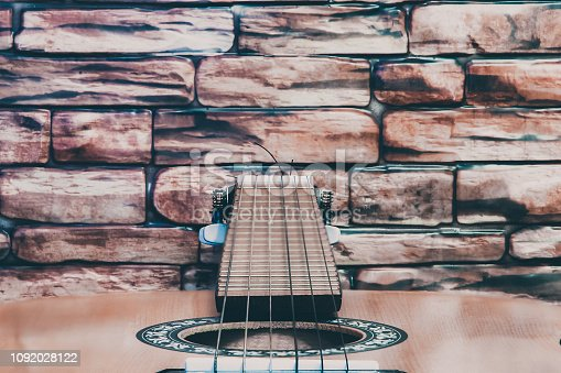 1014432572istockphoto Acoustic guitar on red brick wall background. 1092028122