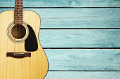 Acoustic guitar on turquoise vintage wooden wall
